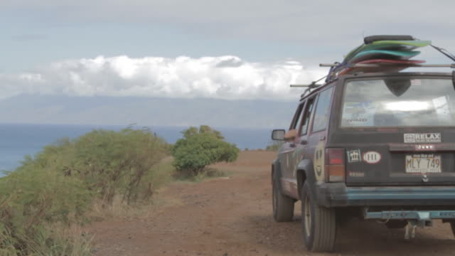 MS Shot of Car with surf boards on top driving down dirt road / Lahaina, Hawaii, United States