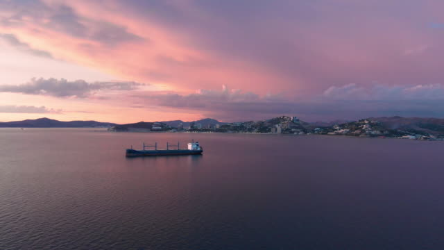shot of cargo ship at sunset with port moresby in the background - papua stock videos and b-roll footage