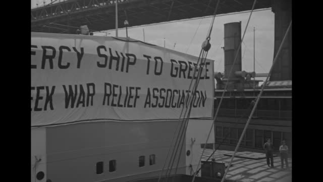 "shot of cargo ship ""sicilia"" next to pier / closer view of banner on front of superstructure of ship reading ""mercy ship to greece, greek war relief... - red cross stock videos & royalty-free footage"