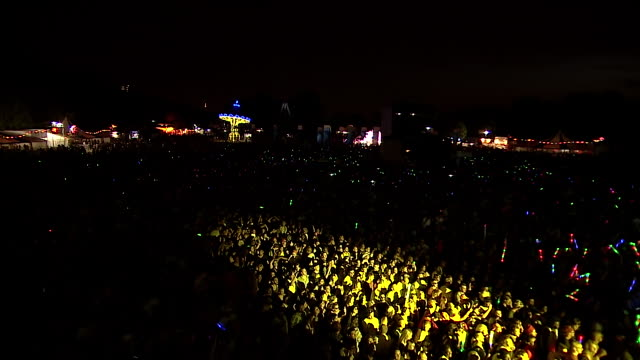 ws cs pov shot of carousel and festival crowd with giant glow sticks at night / victoria park, london, united kingdom - victoria park london stock videos & royalty-free footage