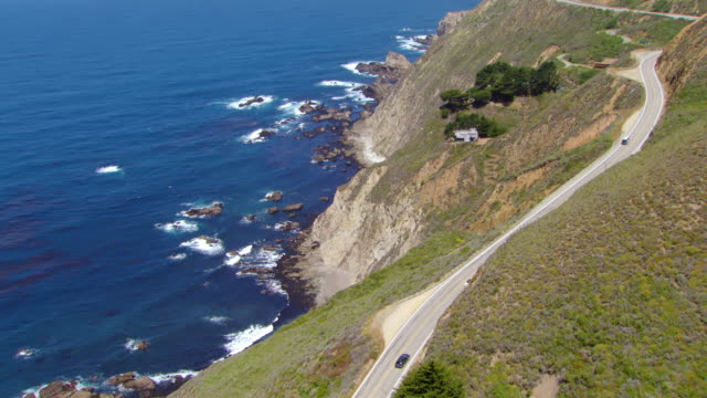 ms zo aerial shot of cars driving on pacific coast highway along pacific ocean / california, united states - route 001 stock videos & royalty-free footage