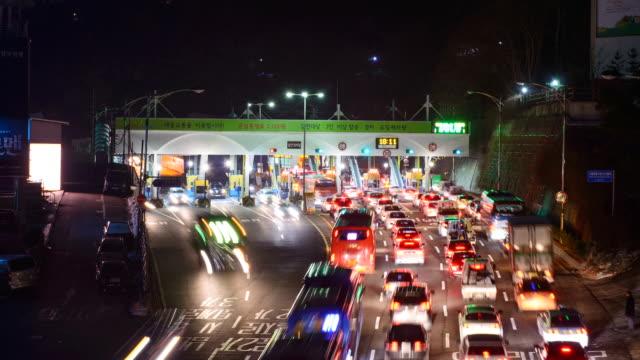 ms t/l shot of cars moving in line at tollbooth  / seoul, south korea - 乗り物の明かり点の映像素材/bロール