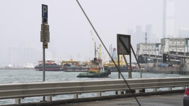 ms shot of cars moving on bridge behind tug boat / hong kong, china - förtöjd bildbanksvideor och videomaterial från bakom kulisserna