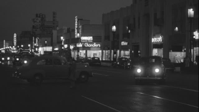 ms pan shot of cars moving on street at night in los angeles - butiksskylt bildbanksvideor och videomaterial från bakom kulisserna