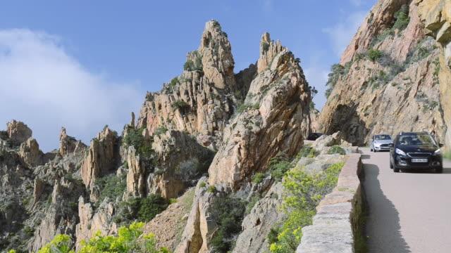 ms shot of cars on the road through the fantastic rock landscape of the calanche of piana, unesco world heritage site / gulf of porto, corsica, france - カランシェ点の映像素材/bロール