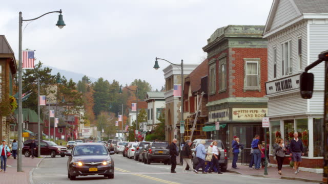 ms shot of cars running and people walking on main street in small town with mountain in distance / lake placid, new york, united states - lake placid town stock videos and b-roll footage