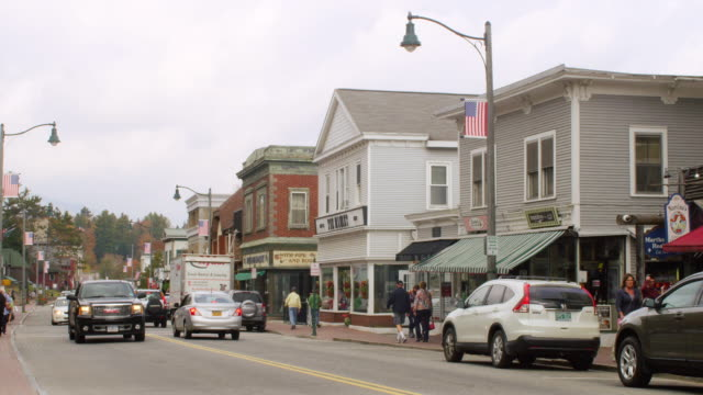 stockvideo's en b-roll-footage met ms shot of cars running and people walking on main street in small town with mountain in distance / lake placid, new york, united states - brancard