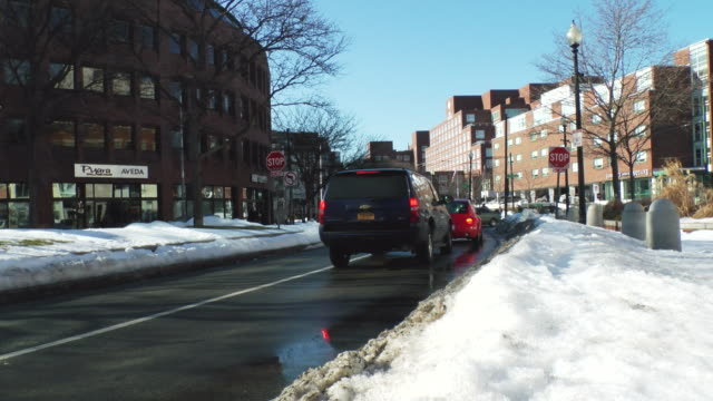 ms shot of cars running on city street with snow covered sides of street / boston, massachusetts, united states - stop sign stock videos & royalty-free footage