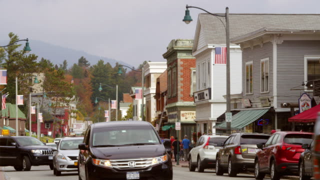 ms shot of cars running on main street in small town with mountain in distance / lake placid, new york, united states - lake placid town stock videos and b-roll footage