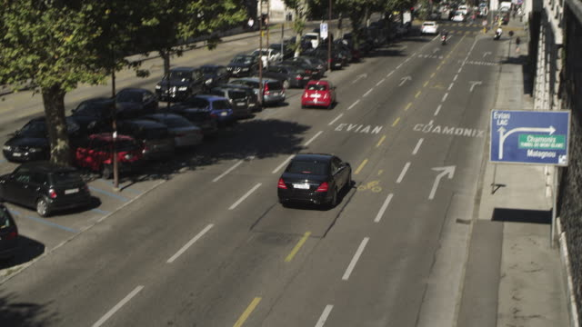 ms tu shot of cars running on road and buildings with parked cars beside / geneva, switzerland - parken stock-videos und b-roll-filmmaterial