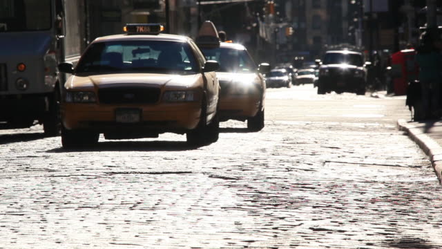 MS Shot of cars running with pedestrians crossing on shining stone pavement street at Soho / New York, United States