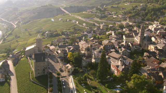 ms aerial ts shot of castle and town hall in village of leuk above rhone valley / leuk, valais, switzerland - kanton wallis stock-videos und b-roll-filmmaterial
