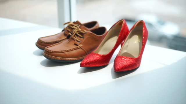 2 shot of casual men brown leather shoes and red high heel women shoes on white background. - dolly shot stock videos & royalty-free footage