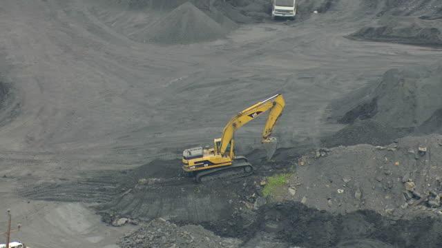 vídeos de stock, filmes e b-roll de cu aerial zo ds shot of caterpillar machine moving dirt at mining valley in schuylkill county / pennsylvania, united states - isolado