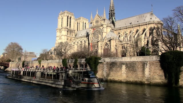 ms shot of cathedral notre dame with boat in river / paris, ile de france, france - ile de france stock videos and b-roll footage