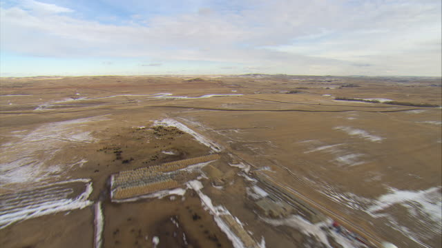 WS AERIAL Shot of cattle ranch and frozen river in Bakken oil field near Watford City / Watford City, North Dakota, United States