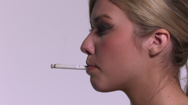 cu slo mo shot of caucasian female head to side smoking cigarette / studio, new york, united states - zigarette stock-videos und b-roll-filmmaterial
