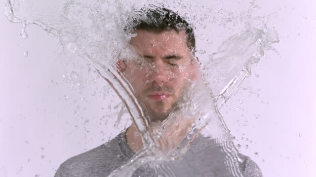 CU SLO MO Shot of Caucasian male against white canvas and water being thrown on him / Studio, New York, United States