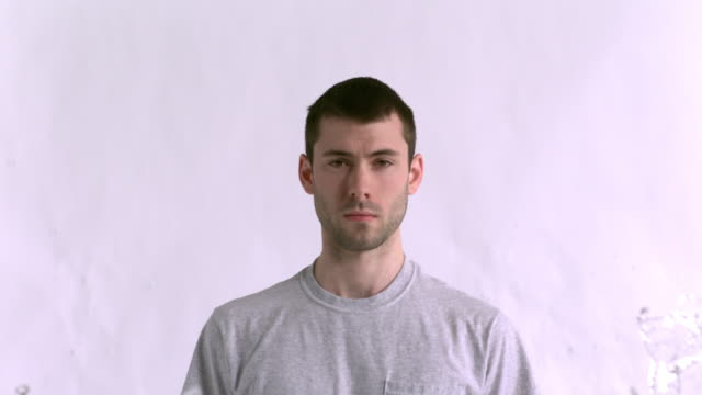 ms slo mo shot of caucasian male against white canvas and water being thrown on him / studio, new york, united states - t shirt stock-videos und b-roll-filmmaterial