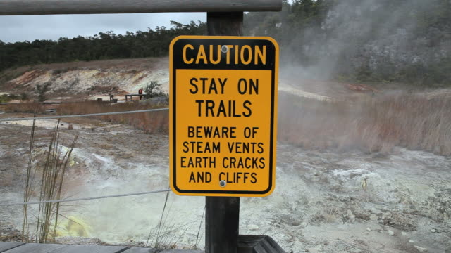 vídeos y material grabado en eventos de stock de ms shot of caution sign at sulphur banks with steam and suplur banks in distance in volcanoes national park / volcano, hawall, big island, united states  - parque nacional