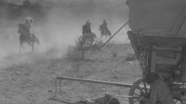 WS Shot of cavalry and Indians ride horseback through terrain and lift up lady on horse