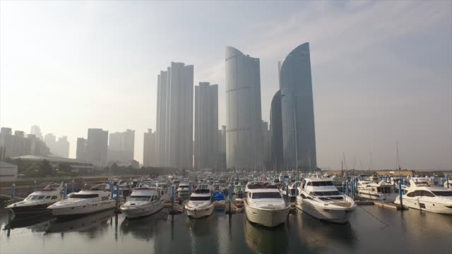 shot of centum city area and boat anchored at suyeong bay in haeundae - anchored stock videos & royalty-free footage