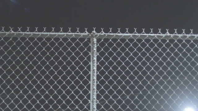 shot of chain link fence at night - chainlink fence stock videos and b-roll footage