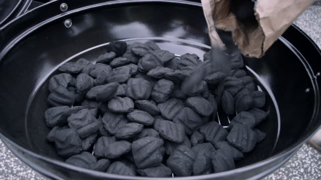 CU Shot of charcoals being poured into grill and then being rearranged / Valhalla, New York, United States