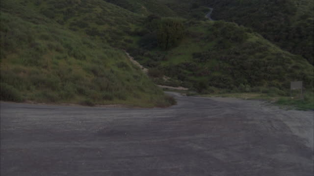 ms ts shot of chase sequence as black cadillac limousine chased by gray cadillac car on mountain dirt road - limousine stock-videos und b-roll-filmmaterial