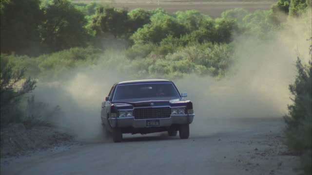 ms ts shot of chase sequence as black cadillac limousine chased by gray cadillac car on mountain dirt road - limousine luxuswagen stock-videos und b-roll-filmmaterial