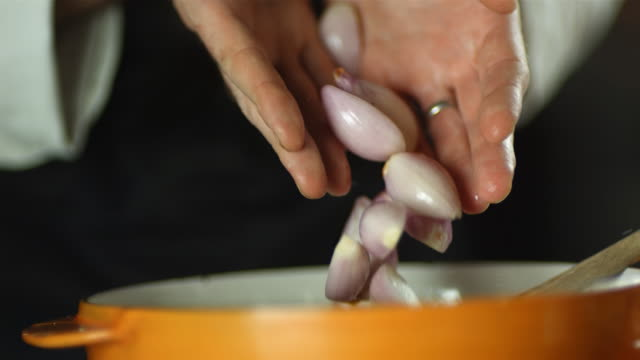CU SLO MO Shot of chef dropping shallots into pan