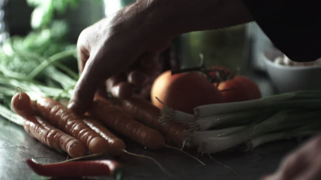 CU R/F SLO MO Shot of chef selecting carrot from collection of vegetables / United Kingdom