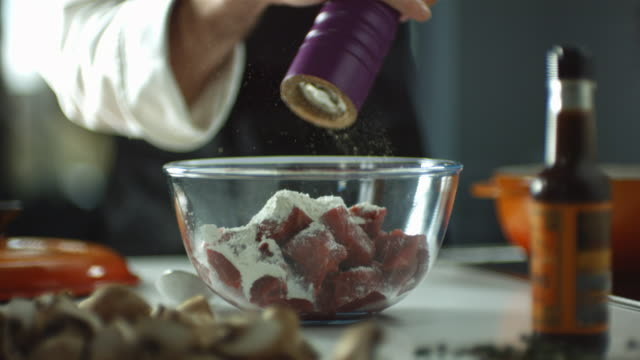 CU SLO MO Shot of chef sprinkling salt on to chopped up beef