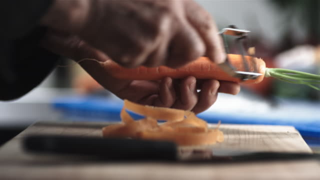 CU R/F SLO MO Shot of chef's hands preparing carrot on chopping board / United Kingdom