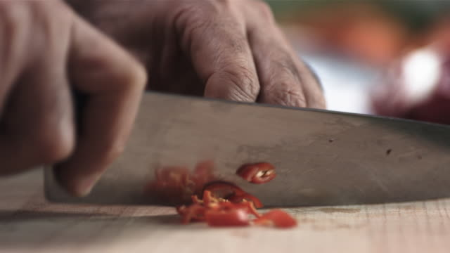 CU R/F SLO MO Shot of chef's hands preparing chili on chopping board / United Kingdom
