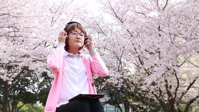 vidéos et rushes de shot of cherry blossoms are in full bloom and woman wearing pink cardigan seated in an tree stump  is listening to music with headphones - cardigan