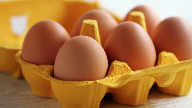 cu  pan shot of chicken eggs in yellow carton / london, united kingdom  - einige gegenstände mittelgroße ansammlung stock-videos und b-roll-filmmaterial