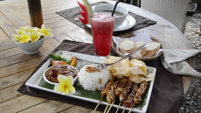 vídeos y material grabado en eventos de stock de ms shot of chicken sate, fried chicken skewer with steamed rice, kerupuk crackers and watermelon juice / ubud, bali, indonesia - cultura indonesia