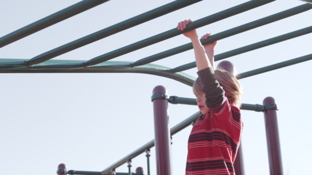 ms ts slo mo shot of child playing on monkey bars on sunny day / beaverton, oregon, united states - parco giochi video stock e b–roll