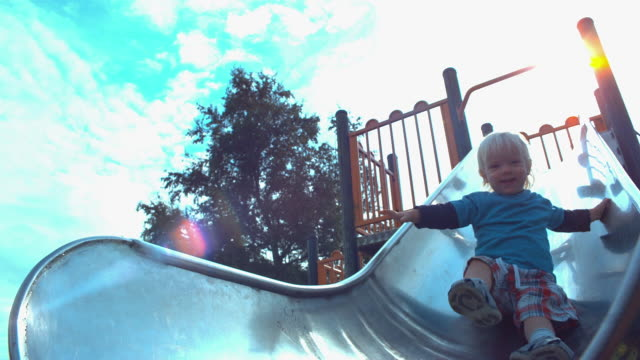 ms slo mo shot of child sliding down slide in park - rutschen stock-videos und b-roll-filmmaterial