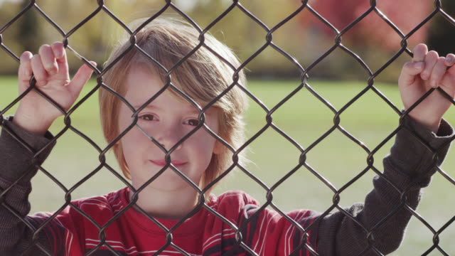 CU SLO MO Shot of child smiling as he looks through chain link fence with sun shines on his back / Beaverton, Oregon, United States
