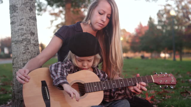 MS Shot of child strums and learns to play guitar with his mom in park / Beaverton, Oregon, United States