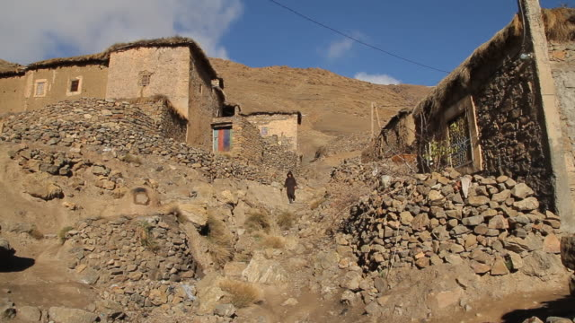 ms shot of child walking down on hilly path on mountainside with homes/ marrakech, tensift, morocco  - wiese stock videos & royalty-free footage