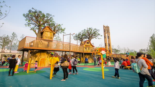 Shot of children and parents playing in playground