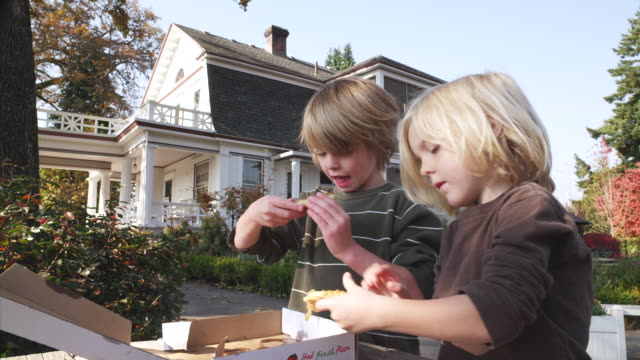 MS Shot of children enjoying pizza lunch outdoors on picnic table in front of large white colonial house / Hood River, Oregon, United States