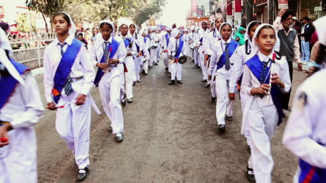 ms shot of children marching in nagar kirtan procession / delhi, india - ドラム容器点の映像素材/bロール