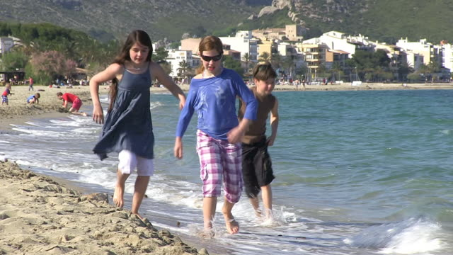 ms zo shot of children playing at beach in holiday / puerto pollenca, mallorca, balearic islands, spain - gemeinsam gehen stock-videos und b-roll-filmmaterial