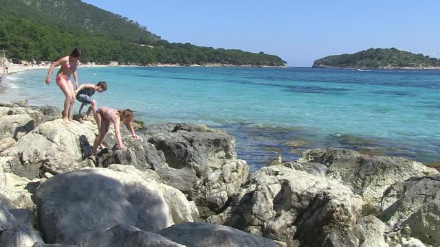 WS Shot of children playing at stony coastline / Puerto Pollenca, Mallorca, Balearic Islands, Spain