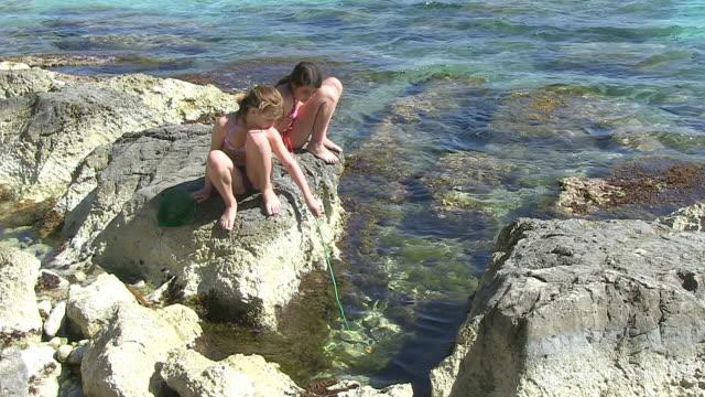MS Shot of children playing at stony coastline / Puerto Pollenca, Mallorca, Balearic Islands, Spain