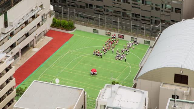 ms t/l shot of children playing in schoolyard / tokyo, japan - 校庭点の映像素材/bロール